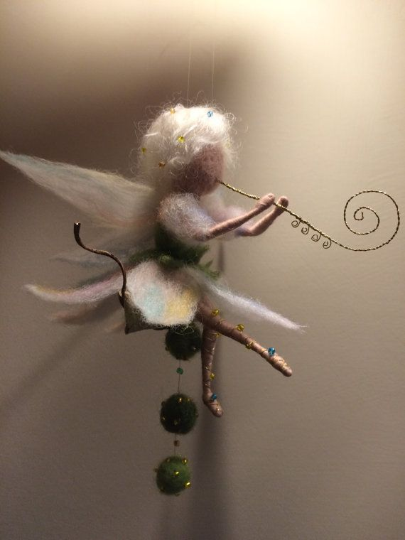 The dress and wings are made of wool is very gentle colored shades. Sandals made of golden thread with beads. The flute made by me from the brass thread. Decor: natural leaf with felting balls. The height of the fairy (sitting) is 13 cm.