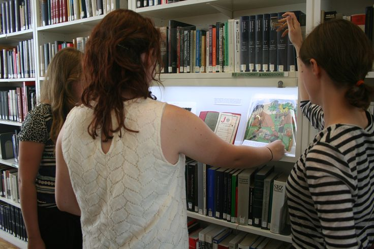 Natalie makes adjustments to a Nazi colouring book on display in one of the cases, illustrating how children and young people were indoctrinated.