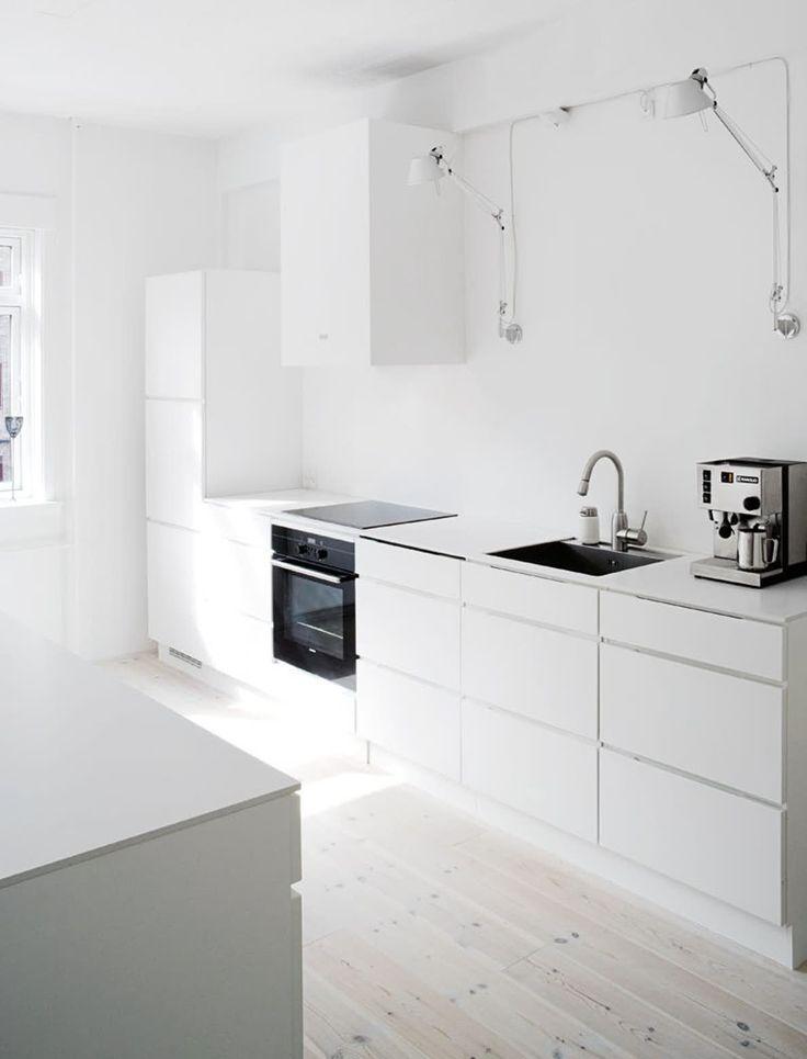 Parret ønskede et hvidt og enkelt køkken, der nærmest skulle svæve bagerst i rummet. De ville ikke have overskabe, og Morten byggede derfor selv en kasse af mdfplader til at skjule emhætten. Det hvide køkken med c...