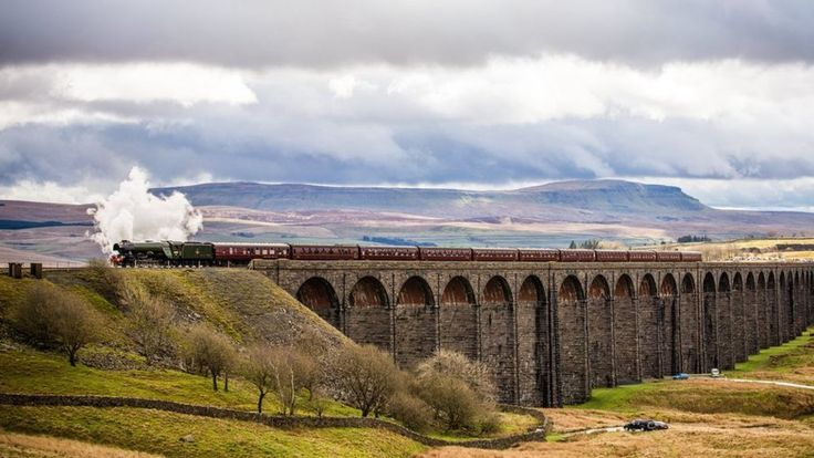 Flying Scotsman's journey through North Yorkshire to Carlisle, crossing the Ribblehead viaduct, marks the Settle-Carlisle railway line reopening after floods