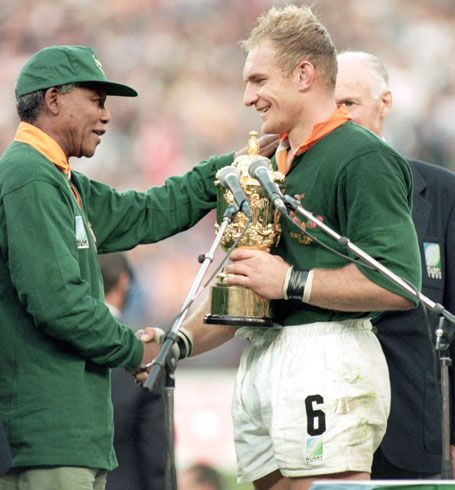 1995: The Rugby World Cup was first major sporting event to take place in South Africa after apartheid. Mandela presented winning trophy to Francois Pienaar, South African rugby captain.