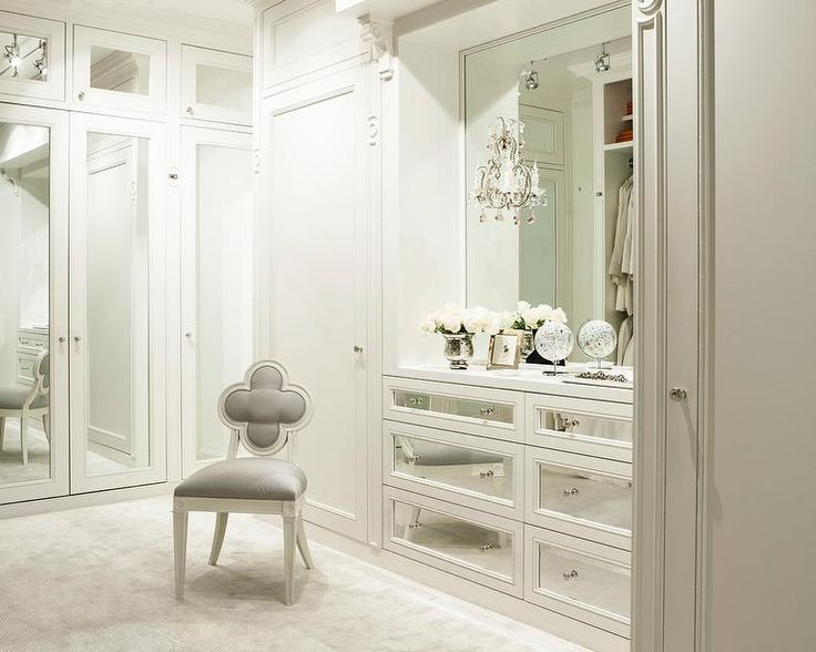 Luxurious white walk-in closet boasts Suzanne Kasler Alexandra Chair placed catty corner in as a wall lined with mirrored wardrobe doors positioned adjacent to built-in mirrored dressers located beneath a white framed vanity mirror flanked by white wardrobe doors.