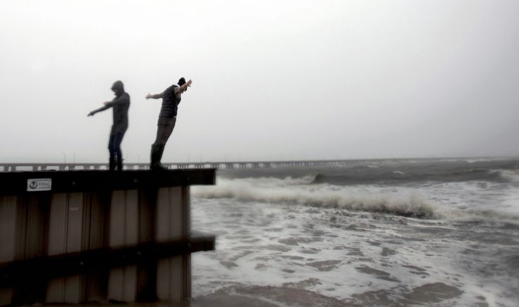 Jessica Ospina, left, and Allison Kane of Virginia Beach, Va., lean into the strong wind and rain off the Chesapeake Bay near the Chesapeake Bay Bridge tunnel in Virginia Beach, vA., as Hurricane Sandy works its way north on Sunday, Oct. 28, 2012. (AP Photo/The Virginian-Pilot, L. Todd Spencer)