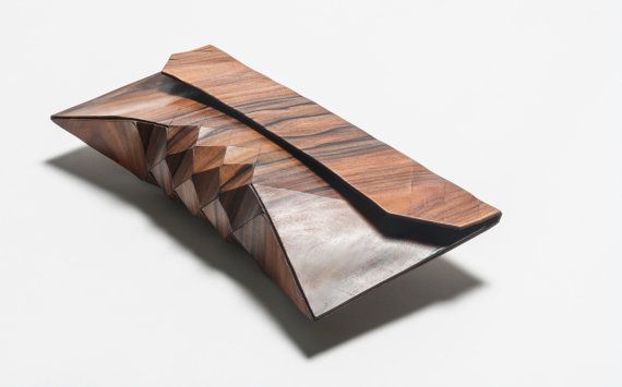 "Wood Clutch - These architectural artisanal ""wood skin"" purses are constructed from 100% wood, 100% hide. While the geometric surface design provides necessary flexibility, the wood texture is soft to the touch, at once both delicate and wear resilient. Timeless yet innovative, these clutches will never go out of style."