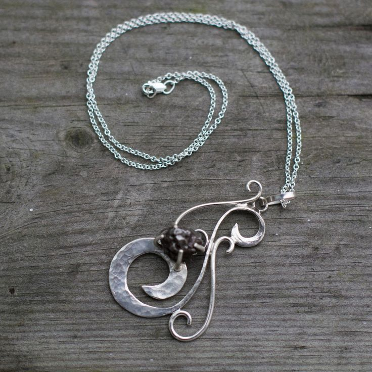 Swirly sterling silver meteorite necklace. I love funky but simple silver jewelry and its even better because it has a piece of real meteorite.
