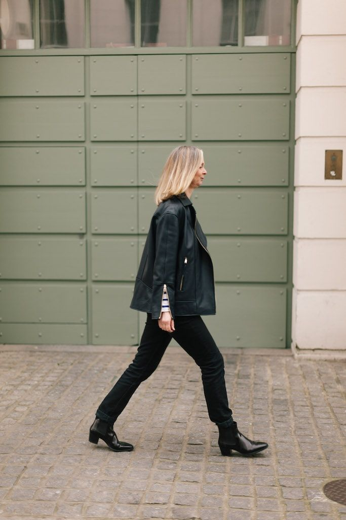 Making strides in black jeans and ankle boots.