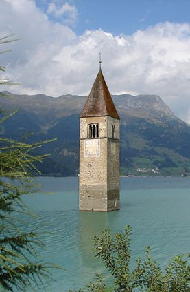 All that remains of this flooded village in Graun, South Tyrol, Italy, is the church tower.  (Photo Credit MaxBisschop via Flickr)