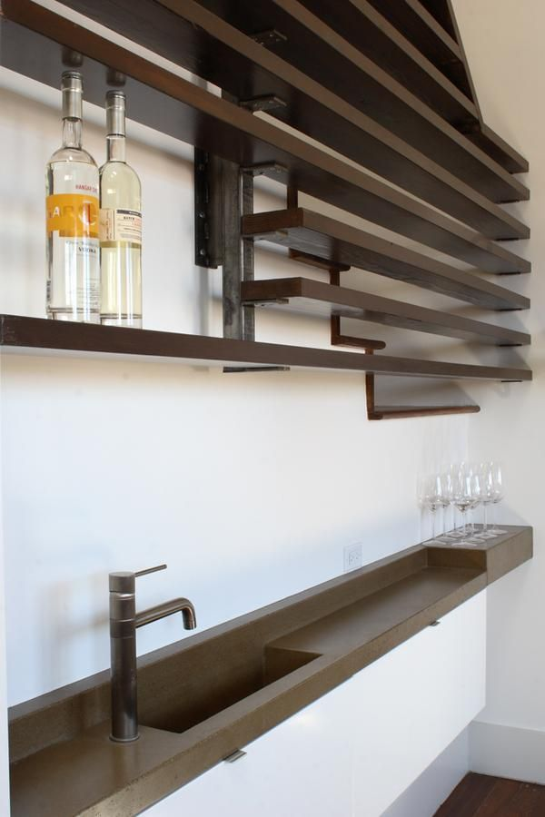 Thin bar created out of sliver space with wood shelves and concrete sink by Medium Plenty, Remodelista