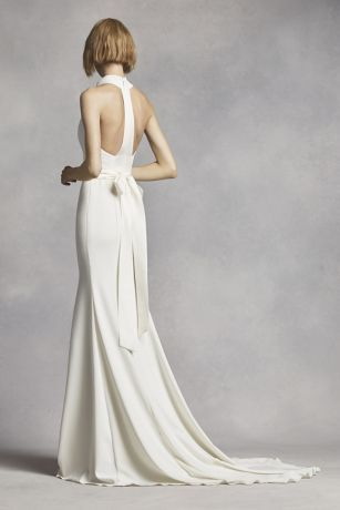This minimalist chic crepe gown will have you looking classicly flawless as you say your I Do's! Halter bodice features a chic, high neckline and contoured seaming detail for an elongated silhoutte. Soft, crepe skirt efforlessly flows for added drama. T-strap racer back takes this contemporary gown to the next level. Simple satin sash adds a classic touch while defining the waist. No train. Sizes 0-26W. Available in select stores and online in Ivory. Plus sizes available for