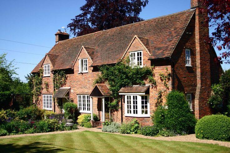 Anglický exteriér na fotografii - to je dokonalá klasika. Cihlové stěny, popínavé rostliny, spousta zeleně a před domem perfektně střižený trávník - dovedete si snad představit typičtější výjev anglické venkovské pohody?