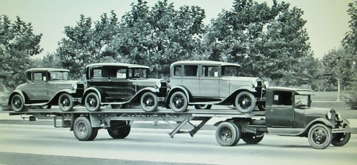 three new 1930/31 Ford model A's loaded on a Fruehauf flat bed trailer and being pulled by a Ford model AA semi tractor.What a great period photo!