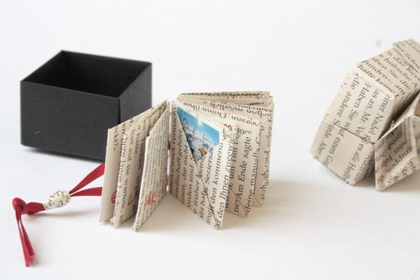They are all individual origami envelopes, like they can be seen for example in Origami Craft by Karen Elaine Thomas. Then she bound these individual pockets in a French stitch pattern onto this slim ribbon that then serves as a closure.