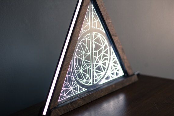 Lumos! Built with a sturdy batlic birch frame and coupled with an engraved acrylic. Each side of the triangle measures 12 inches, making it a great show piece that casts soft light around the room. The lamp is illuminated by six ultrabright white LEDs housed in the base of the lamp.