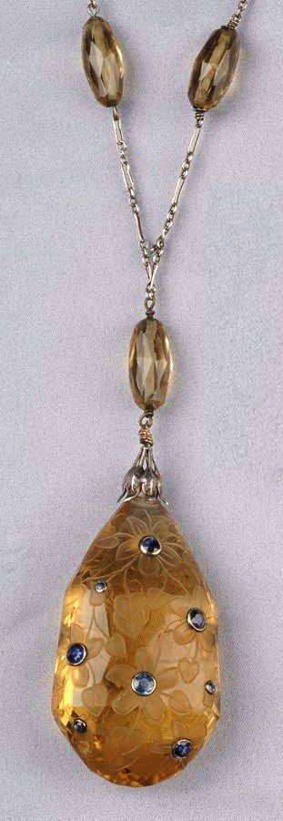 Art Deco Citrine and Sapphire Pendant, the shaped citrine drop set with circular-cut sapphires, and allover floral engraving, with silver foliate cap, and suspended from paperclip chain with faceted citrine beads, together with a 14kt gold and citrine bead extension, pendant lg. 2 3/8 in.
