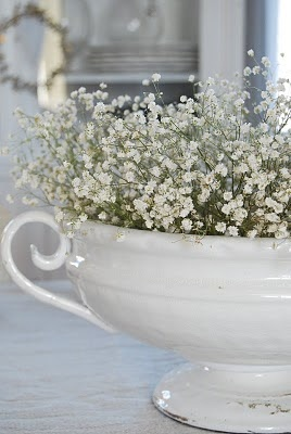 Baby's breath in a white urn.  What could be more perfect?  I would put this on either a rustic table or one with a freshly ironed white cloth.