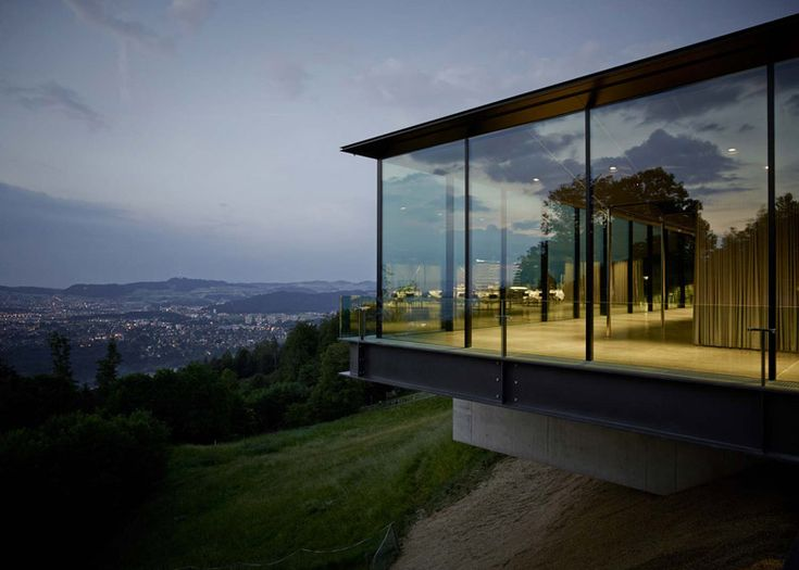 Exterior curtains draw back across the glazed facade of this hillside events venue in Bern, Switzerland, to offer visitors uninterrupted views of the surrounding Alps .