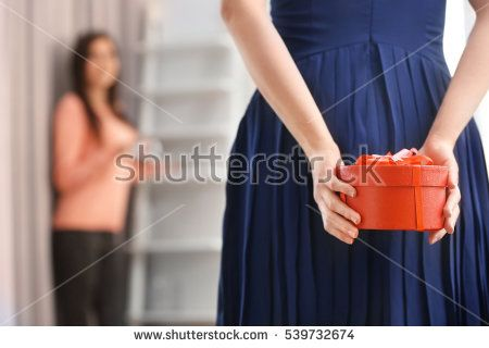 Woman hiding box with present behind her back, closeup