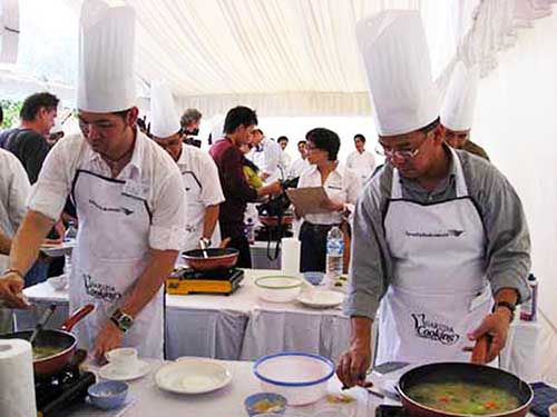 TV personality Ferry Salim and Garuda chief executive officer Emirsyah Satar (right) take part in a cooking competition ...