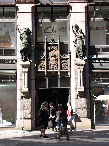 Julkisivun Kehruu ja metsästys -aiheiset veistokset laati Robert Stigell.Nykyisin talo on suojeltu, historiallisestikin merkittävä rakennus. Kehruu ja Metsästys (Spinning and Hunting) statues at the main entrance of Aleksanterinkatu 13. Sculpted by Robert Stigell in 1900. Photo MKFI