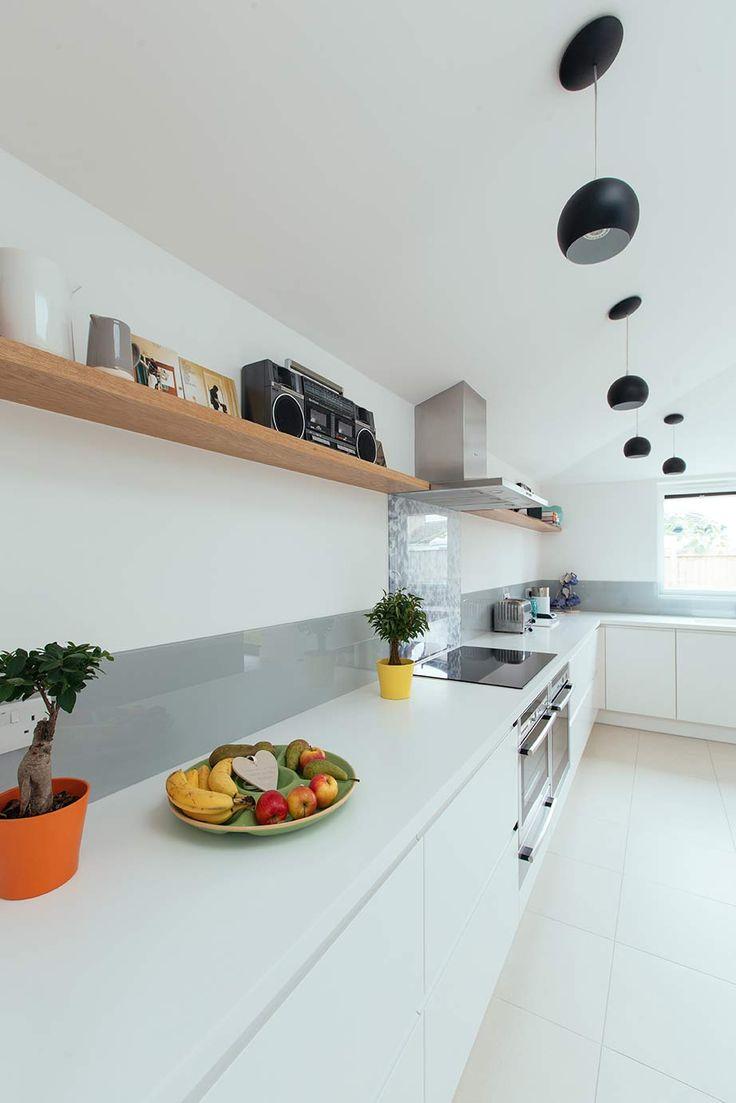 Corian worktop kitchen with matt white units. Grey glass splashback.