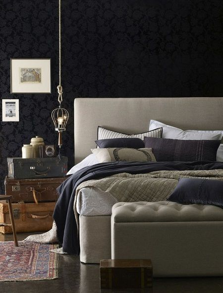 playful antique luggage nightstand, bold walls, classic rug and a mixture of deep blues and neutral textiles