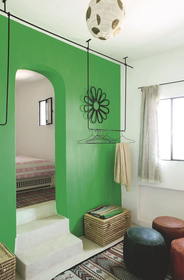 Dans les chambres du bas, le vert arabe est adouci par un kilim et un dessus-de-lit dans les tons rose pâle.