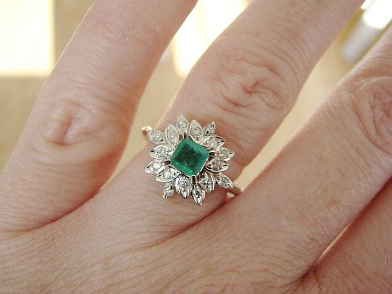 This Stunning Vintage 1950s Ring Features a Platinum Flower Halo Setting. Set with .10 Carats of Natural Diamonds and an Amazing .42 Carat Natural Emerald. Make any Girl Happy with this Ring as an Engagement or Right Hand Ring!! Size 5.25 Can be re-sized