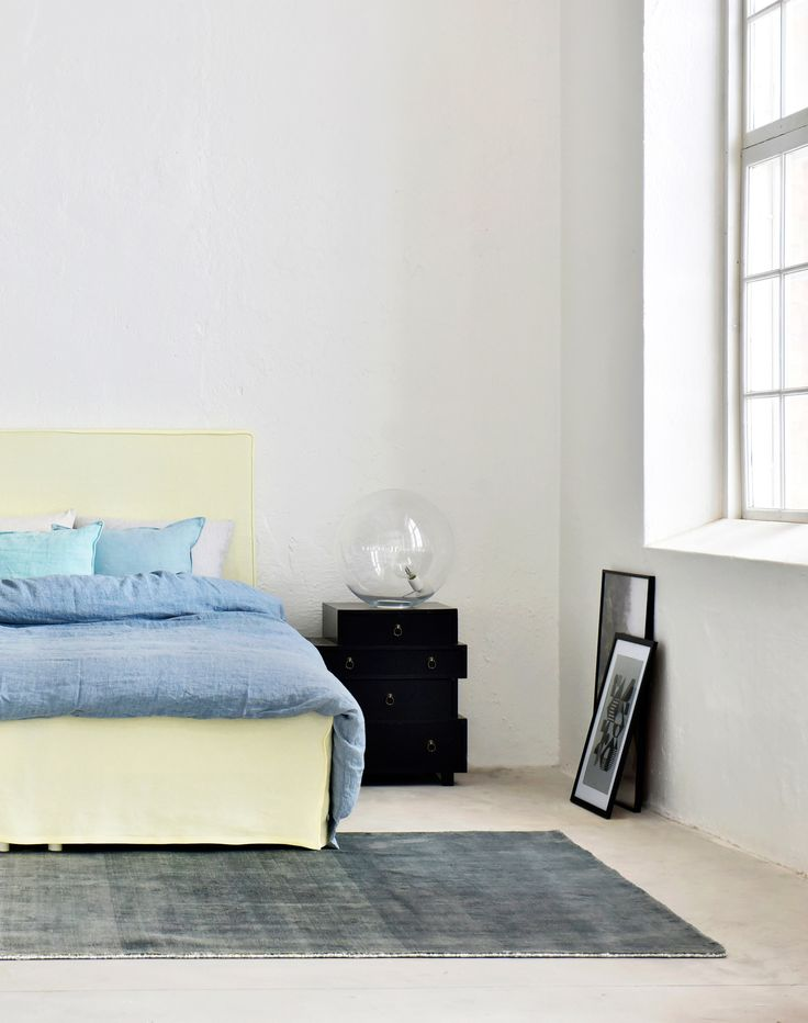 Industrial loft style apartment with huge windows | modern minimal bedroom | pastel bedroom | pale yellow headboard and bedskirt | IKEA Abelvär headboard with a Bemz cover | Did you know that Bemz offers a wide range of bedroom textiles