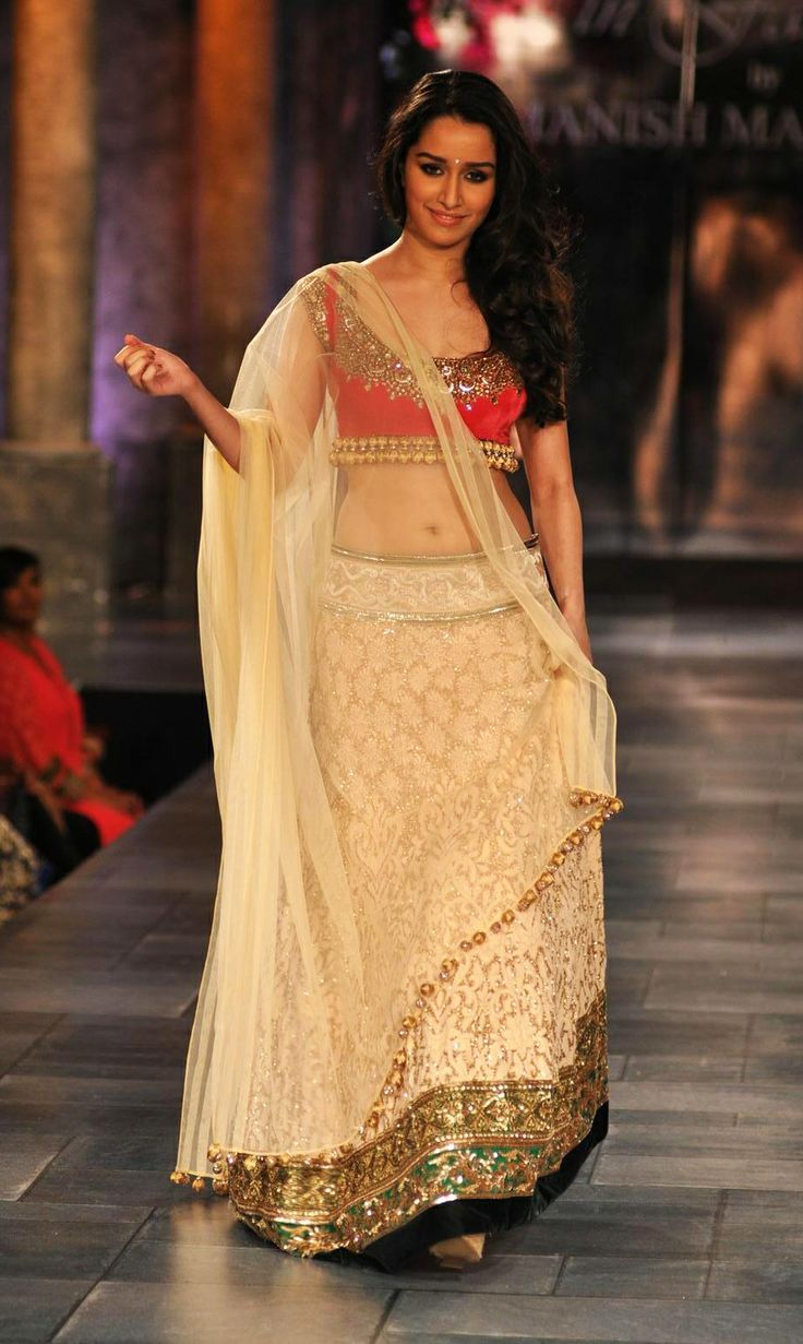 Shraddha Kapoor in a plain flared net skirt bridal lehenga with sophisticated silver and golden touch worn with a tomato red blouse and a plain dupatta at the Mijwan Welfare Fashion Show. Source: rediff.com
