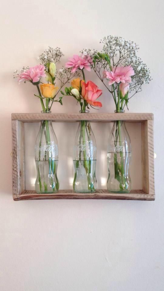Pallet wood and glass coke bottles used to create a wall mounted vase! www.littlesheepcorner.co.uk