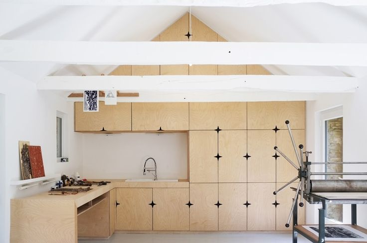 When an old Breton barn in France was converted into an artist studio, Modal Architecture designed the space to include birch plywood cabinetry. The cabinets made by Yvon Le Houerou, a local carpenter, feature a star-shaped cut out in place of where the door pulls would be.