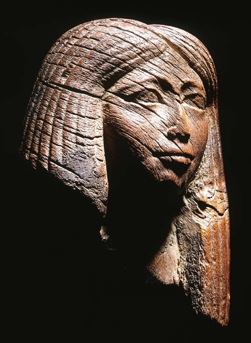 AN EGYPTIAN WOODEN HEAD OF AN IMPORTANT EGYPTIAN NOBLEWOMAN   LATE DYNASTY XVIII/EARLY DYNASTY XIX, CIRCA 1300 B.C.   Wearing a tripartite wig, with central parting and finely striated braids, with a serene expression and sensitively modelled eyebrows, eye-line and pupils, on velvet mount  5½ in. (14 cm.) high