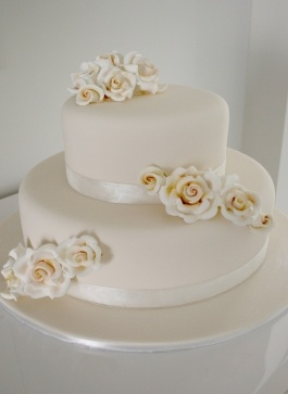 Two tier ivory iced wedding cake with ivory sugar roses by Classic Cakes www.classiccakes.com.au