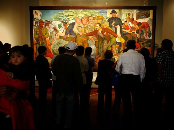 "Mexico City Must-Dos by National Geographic | Art lovers view Mexican artist Diego Rivera's ""Glorious Victory,"" on display at Mexico City's Palacio de Bellas Artes."