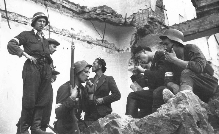 Warsaw Uprising, August 1944: Polish insurgents take a cigarette break in the ruins of the central post office on Napoleon square. Note the German helmets and rifle.