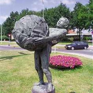 """Oldenzaal Boeskoolstad, Bronzen beeld van een man met een grote kool (Boeskoolmenneke). Kunstenaar was Jan Kip (Oldenzaal 1926-Oldenzaal 1987) beeldhouwer en edelsmid. Oldenzaal wordt ook wel de Boeskoolstad genoemd. Deze naam dankt de stad en haar inwoners aan het boeskoolmenneke. Vroeger werd door de plaatselijke bevolking de """"boeskool"""" (witte kool) veelvuldig op het land verbouwd en op de markten in omliggende steden aangeboden of als betaalmiddel gebruikt."""