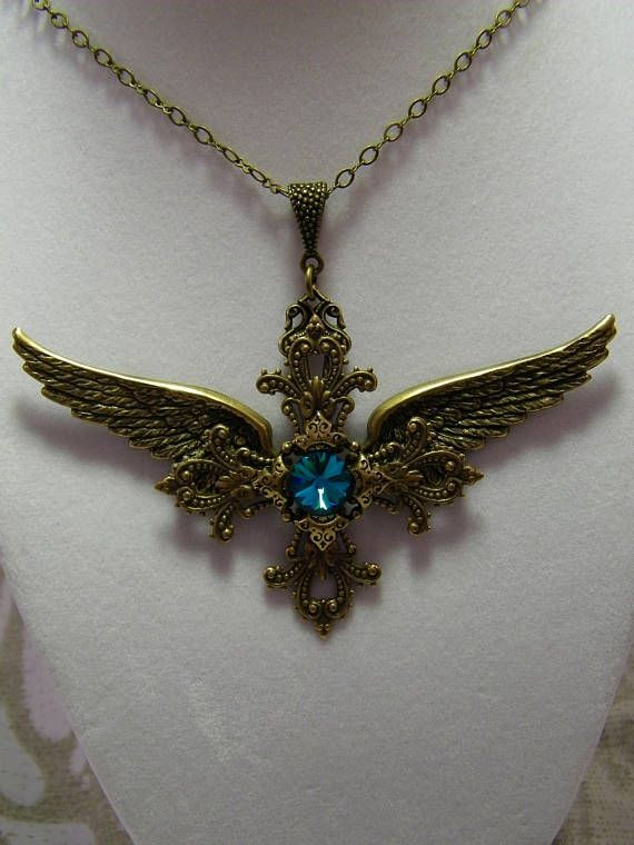 From Glory to Glory, gorgeous 10mm Swarovsky Blue Zircon Rivoli mounted between 4 Crowns centered on a Maltese Cross between Angels wings. Simple Elegance.  Heart and Wings charm dangles from back at Lobster Clasp.  Chain is 18 inches in length.  Made in a smoke free home. Lead and Nickel free components.