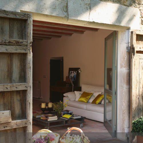 Die Blumenkörbe auf der Terrasse bringen Lust auf den Sommer und passen zum mediterranen Einrichtungsstil. Die rustikalen Holzläden und die Natursteinwand…