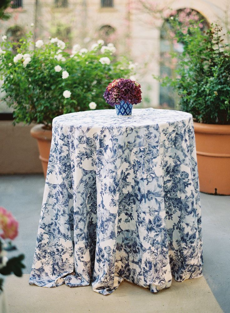 Small, round cocktail tables swathed in French blue floral linens and topped with small arrangements of lush hydrangea blossoms dotted the terrace. #WeddingDecor Photography: Jose Villa Photography. Read More: http://www.insideweddings.com/weddings/incredible-rooftop-rehearsal-dinner-with-striking-striped-tent/555/