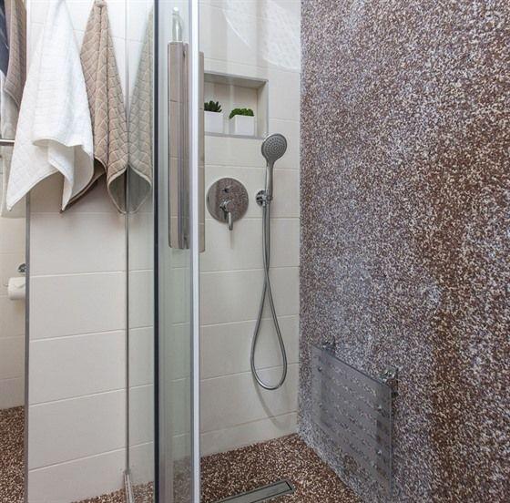 Na podlahu i stěnu sprchového koutu byl použitý takzvaný kamenný koberec (Topstone), nechybí sklopné sedátko a madlo pro bezpečné užívání.