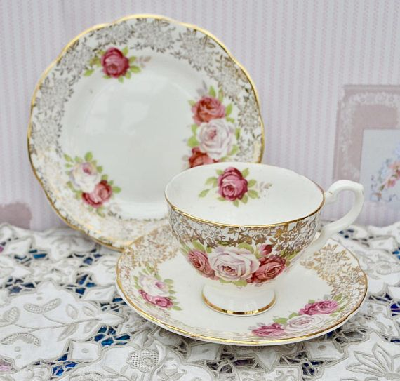 Vintage bone china tea trio made by English china company Bowbell, likely manufacture date 1940s - 1950s. The trio consists of tea cup, saucer and tea plate in antique white with a border of gilding in a lace like pattern. There is further gilding to the edges of all pieces and foot and handle of the tea cup. All of the pieces are decorated with a pink roses in different shades of pink and varying size of bouquet and repeated on the interior of the cup. There is shade variation in the roses…