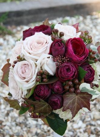 実を添えたシックカラーのラウンドブーケ 深い赤のオールドローズに、シルバーがかったピンクのバラ。その間から沢山顔を出すヒペリカム(実)と、添えられた茶や淡いグリーン。深まる秋や冬の済んだ空気が似合うラウンドブーケです。季節ごとにアクセサリーを変えるように、季節らしさをドレスにも取り入れることでお洒落感もグッとアップします。よく見る色ではないものが好き、大人っぽいスタイルを目指したい、という方にオススメです。