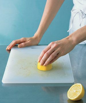To remove tough food stains from light wood and plastic cutting boards, slice a lemon in half, squeeze onto the soiled surface, rub, and let sit for 20 minutes before rinsing.