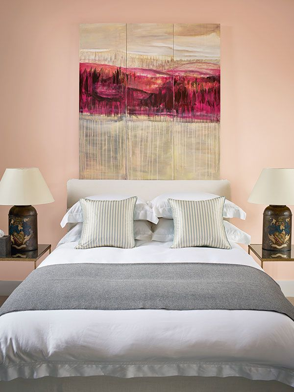 A combination of dusky pink walls, grey blue silk striped cushions and a soft grey throw work together to create a bedroom so sumptuous, it makes you long for bed.