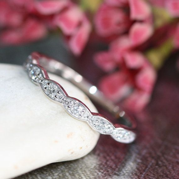 This vintage inspired wedding ring is crafted in a solid 14k white gold half eternity band studded with brilliant conflict free diamonds. This