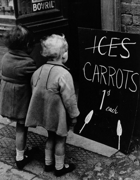 Two little girls read a board advertising carrots instead of ice lollies due to wartime shortages of chocolate and ice cream, 1941.