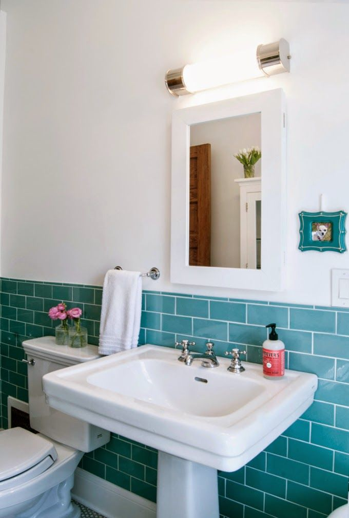 Vintage yet still modern. Turquoise subway tile, white sink, medicine cabinet, retro light fixture and a chandelier. Love the puppy pic.