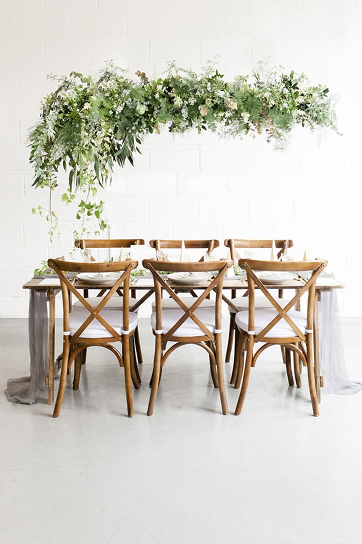 Light and airy organic wedding tablescape with greenery hanging florals, cross-back wooden chairs and beautiful silk linens