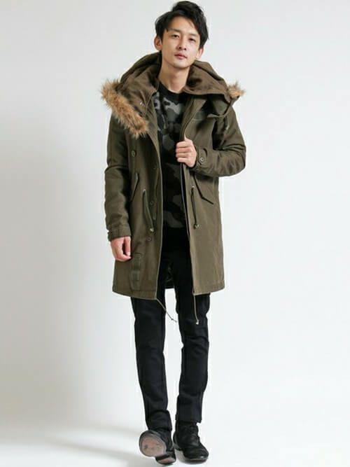 ファーのついたカーキのモッズコートを迷彩カットソーと合わせて着こなす男性