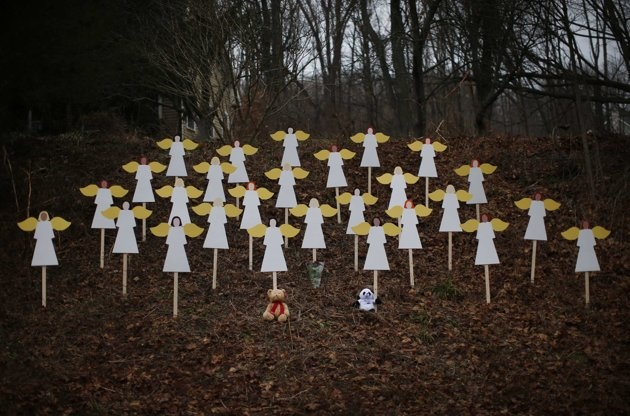 Twenty-seven wooden angel figures are seen placed in a wooded area beside a road near the Sandy Hook Elementary School for the victims of a school shooting in Newtown, Connecticut December 16, 2012. Twelve girls, eight boys and six adult women were killed in the shooting on Friday at the Sandy Hook Elementary School in Newtown.